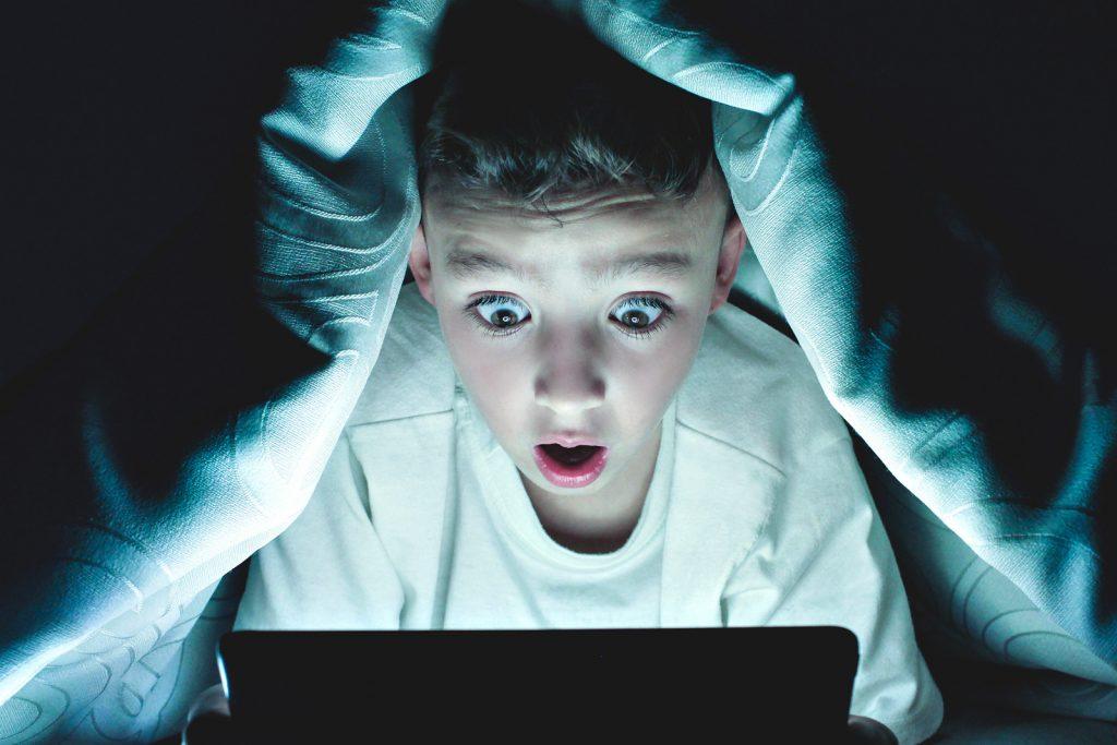 storytelling - pojke tittar på ipad under täcket